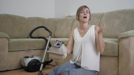 arrumado : allergy to hygiene, a woman sitting on floor sneezes due to dust after cleaning room with a vacuum cleaner Stock Footage