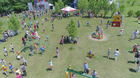 оставлять : KOZACHI LAGERYA, UKRAINE- JUNE 01, 2019: children public holiday, kids with parents joyfully spend time in parkland during child day celebration Стоковые видеозаписи