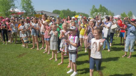 rejoices : KOZACHI LAGERYA, UKRAINE- JUNE 01, 2019: ovation, crowd of happy children active clap their hands while standing in clearing after concert dedicated to Children Day