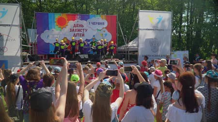 rejoices : KOZACHI LAGERYA, UKRAINE- JUNE 01, 2019: Children Protection Day, crowd of fun kids watching performing children hip-hop dance on stage during holiday celebration on vacation in park