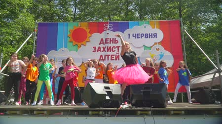 rejoices : KOZACHI LAGERYA, UKRAINE- JUNE 01, 2019: charity festival, cheerful children have fun dancing with animator on stage during a concert to celebrate Childrens Day on weekend Stock Footage