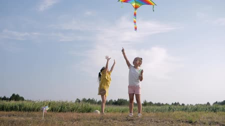 cometa volando : outdoor games, cute cheerful girls friends spend carefree time in clearing launching kite rejoicing and having fun with wonderful vacation in countryside