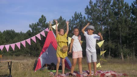 lodge : funny childrens games, joyful emotional kids merrily spend time actively and joyfully dance and sing in a meadow decorated with a wigwam during a summer vacation in the forest