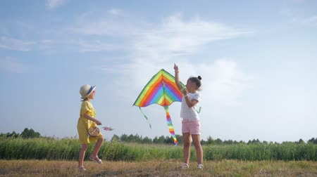 juntar : girls play with a kite, little happy girlfriends get along with spending time outdoors playing with an air toy in forest glade during summer vacation