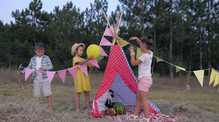 домик : friends decorate a glade with wigwam in a forest for a picnic during a weekend in the countryside, happy childhood