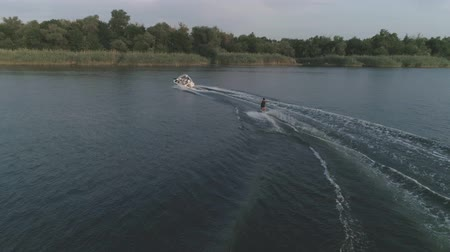 моторная лодка : active lifestyle, aerial view athlete surfing on his wakeboard along the river behind a motor boat at evening outdoor in slow motion