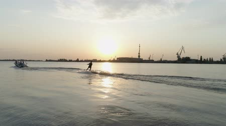 vest : aerial view, surfer man rides on his wakeboard along river behind motorboat and holds rope handle in hands during sunset