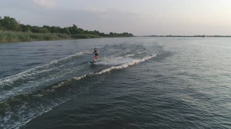 моторная лодка : drone shot, athletic man rides on his board behind motorboat with splashes water along river during summer holiday at nature Стоковые видеозаписи