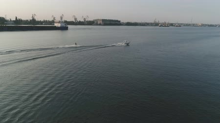 lancha : drone view, sportsman in life vest rides on wakeboard along river holding rope tied to powerboat on background of port in slow motion outdoor