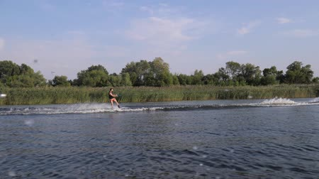 vest : extreme sport, surfer man rides on his board behind motorboat on river with splashes water on background nature and blue sky