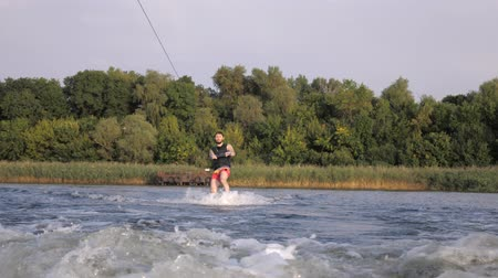 kamış : happy wakeboarder rides on his board behind motorboat with splashes and holds rope handle, sporting man training on river during weekend Stok Video