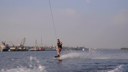 kamış : smiling surfer man rides on his board behind motorboat with water splashes outdoors on background of port and blue sky in slow motion