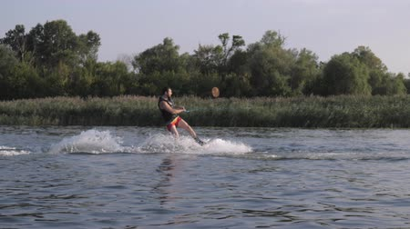 моторная лодка : sportive man wakeboarder training on his board behind motorboat with water splashes along river on background of reeds in slow motion