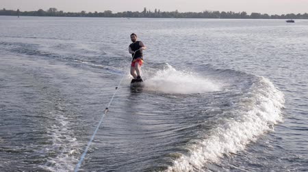 kamış : surfing, cool sportsman rides on his board behind motorboat on river with splashes water on background nature