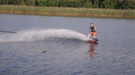 lancha : wakeboarder man holds rope handle and rides on board on river in slow motion with water splashes on background of reeds and trees Vídeos