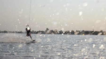 vest : wakeboarder rides on his board behind motorboat and holds rope handle during summer evening on river, lot splashes water