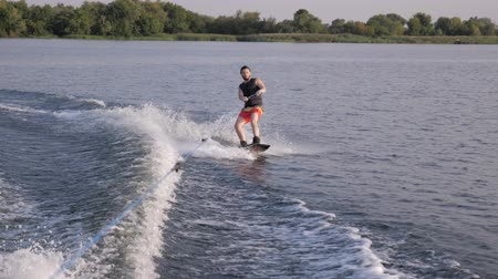 kamış : water extreme sport, wakeboarder man holds rope handle and rides on his board on river in slow motion with splashes on background of nature