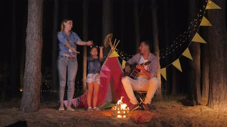 petite : family fun, happy father plays guitar for mom with a daughter which are dancing at campfire during summer weekend in forest on background of wigwam