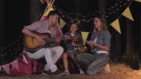 lunchen : family in forest, young parents with their female child have fun playing guitar and eating fruits at night picnic in forest backdrop of wigwam Stockvideo