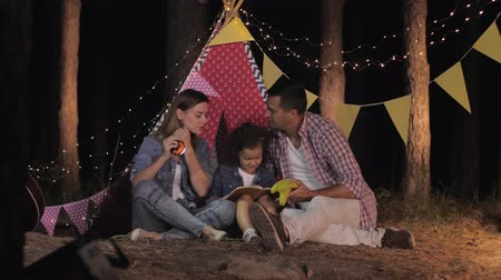 petite : family weekend, caring father brings fruit snack to his family during a picnic in forest on background of wigwam