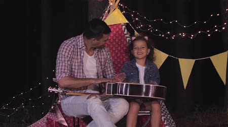 стучать : happy parenthood, dad with daughter knock on guitar like by drum sitting beside wigwam with flags and garlands at evening during recreation in forest