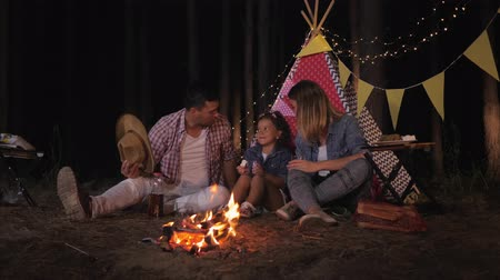 parentes : relatives on picnic, joyful little handsome girl with parents listens cheerfully to funny stories and drinks juice by fire on background of wigwam while camping in forest Stock Footage