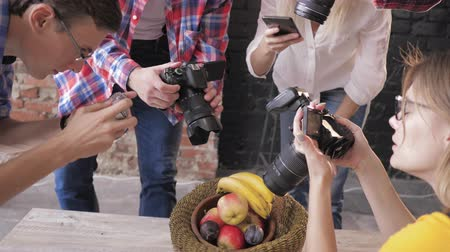 fotoshoot : active photographers at a master class take pictures of fruits in a basket on a wooden table using cameras and a cellphone, close up