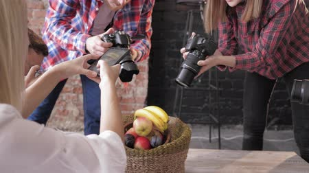 fotoshoot : cameramans learn to take pictures of fruits in basket on a wooden table use cameras and a mobile phone during master class, closeup