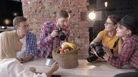 fotoshoot : learning photography, cameramans with cameras and a mobile phone take pictures of still life during master class in studio Stockvideo
