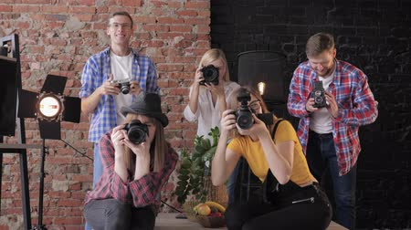 fotoshoot : many photographers on the masterclass take pictures on camera then raise their hands and smile on the background of a brick wall in studio