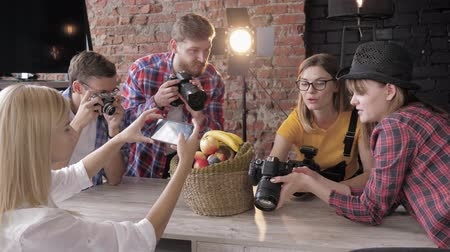 fotoshoot : master class with equipment in a studio, young photographers learn to take pictures of fruits in a basket with use cameras and mobile phone