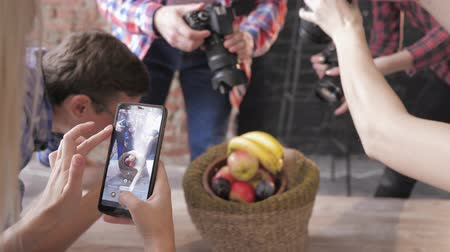 fotoshoot : modern operators use cameras and a mobile phone to take photographs of fruits in basket on a wooden table during master class