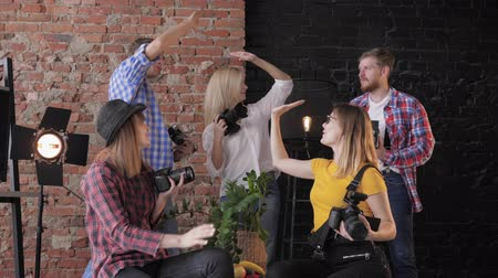 fotoshoot : photographers giving a high five to each other after a successful masterclass with cameras in hands on the background of a brick wall, photo studio