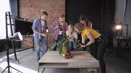 television set : photographers with professional cameras and mobile phone take pictures of fruits and flowers on set of photo studio using softboxes, slow motion