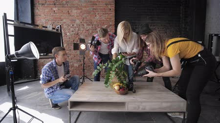 television set : photographers with professional cameras and mobile phone during masterclass take pictures of still life on background of softboxes and brick wall Stock Footage