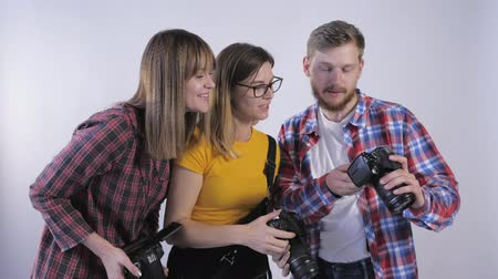 viewfinder : company of professionals with digital cameras in their hands studying the pictures taken in photo studio during a seminar for photographers Stock Footage