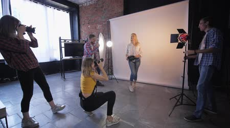 fotográfico : fashion photography, a group of professionals with digital cameras take photos of a beautiful model in a photo studio Stock Footage