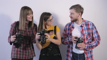 professional photography : group of professionals photographers with digital camera study technical specifications cameras during workshop in photo school