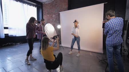 fényképész : photo workshop, a company of creative photographers takes pictures of a young model during training in studio shooting