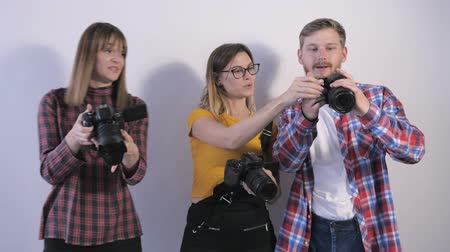 fotográfico : young professionals with digital cameras in their hands discuss pictures made during a seminar for photographers in a photo studio Stock Footage