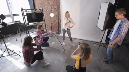 professional photography : fashion session, a group of young creative people learn studio shooting during photography workshop on background of lighting lamps