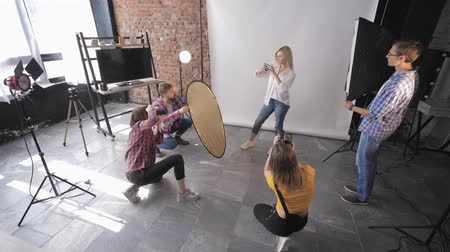 professional photography : fashionable session, group of photographers with assistants take pictures in a professional studio with beautiful girl model Stock Footage