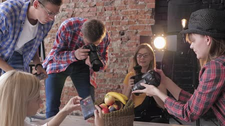 istantanea : hobby photography, a professional photographer conducts a master class on photo shooting food for young creative people in a fashion studio