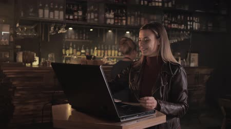 taberna : visitor at bar, an attractive woman freelancer works at computer in bar while barista brings her coffee, small business concept Stock Footage