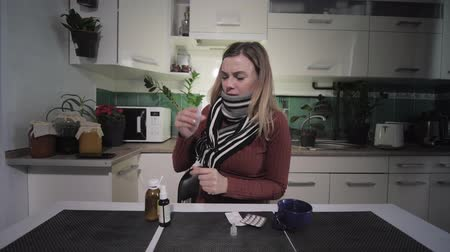 zsebkendő : woman suffers from a cold, freezes due to temperature in kitchen, tormented from stuffy nose and receives drops from villain Stock mozgókép