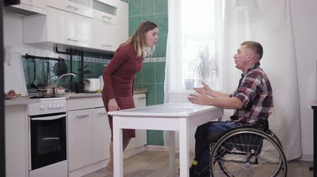 nervous breakdown : couple of quarrels, a disabled person in a wheelchair scandalously swears with his aggressive wife and shout at each other aggressively wave their hands to find out the relationship