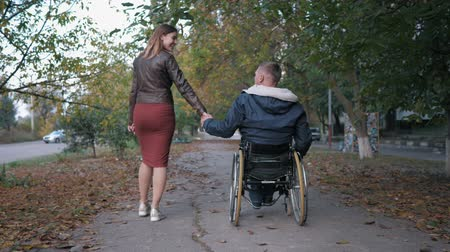 inwalida : beloved disabled person in a wheelchair holds his wifes hand while walking in the autumn park amid trees