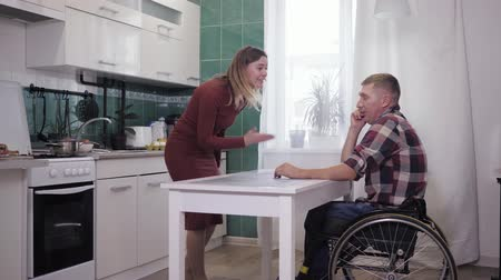 desfocado : couple quarreling, disabled male in a wheelchair scandalous swears and screams at each other figuring out a relationship