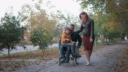 inwalida : disabled man in a wheelchair rides a boy on the cradle while walking along the autumn street with his girlfriend
