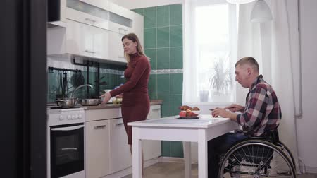 paralysé : family atmosphere, a husband in a wheelchair cooks in the kitchen with his loving wife